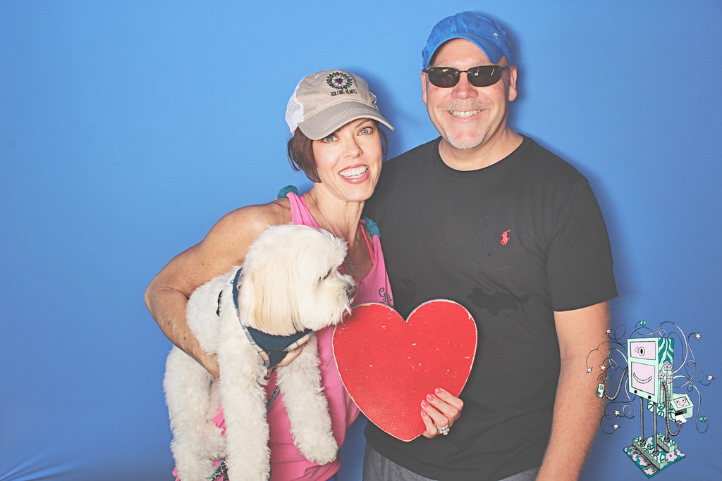 GG standing beside her husband and holding a white puppy in her arms.  The other hand is holding a big red heart