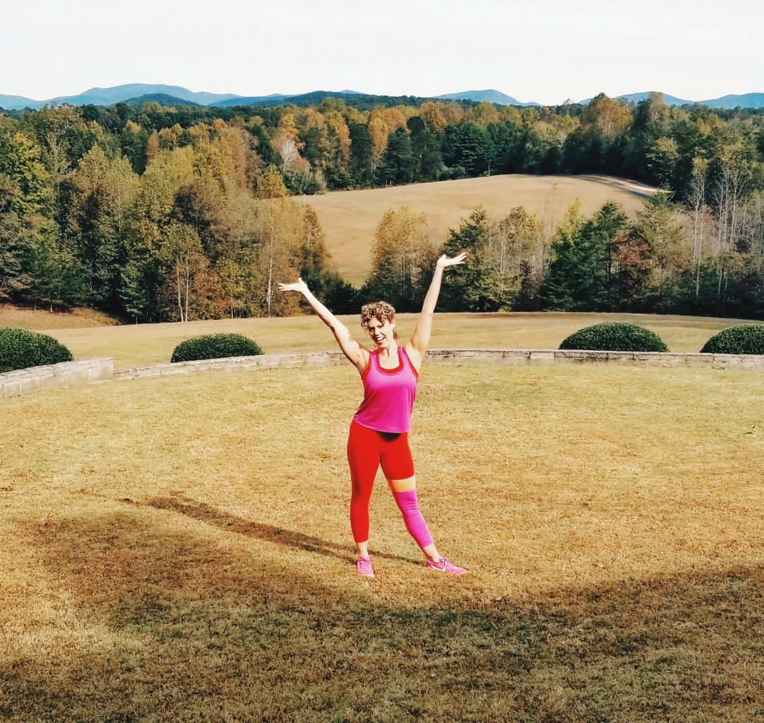 picture of green grass and mountains in the background and GG standing in the middle with a workout outfit on and arms stretched us