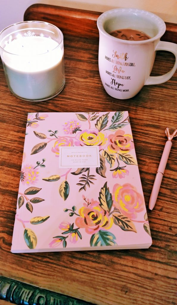 pink floral journal and a pink pen on a table with a candle and a cup of coffee