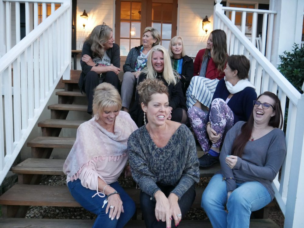 Women staggered on steps of a house outside laughing really hard