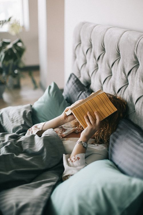 picture of a girl on a bed with a book over her head