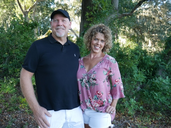 GG and her husband standing together in the yard