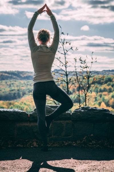 woman starting out to look at mountains and she is in a yoga pose, tree pose