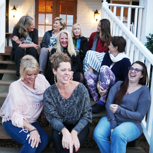 women sitting on stairs at a big southern home and laughing