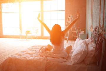 girl sitting on a bed waking up with the sun shining into her window