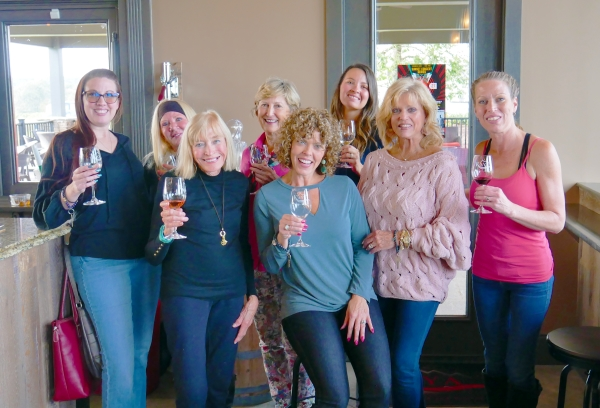 8 Women at a winery drinking wine and looking at the camera