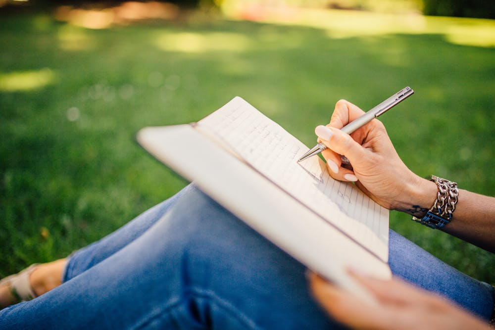 woman sitting on the grass journaling