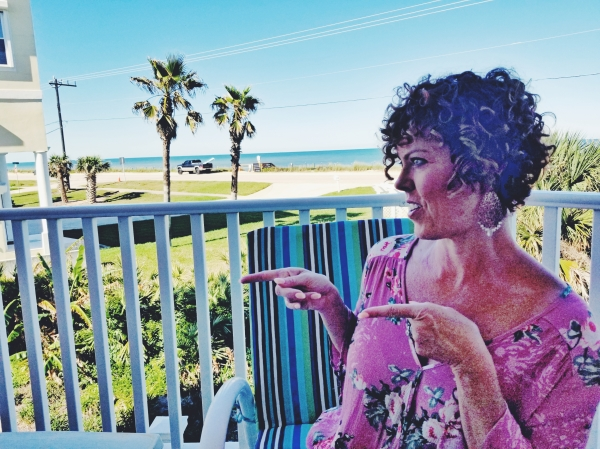 GG on her patio overlooking and pointing to the ocean
